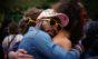 Drie vrienden knuffelen. Ze dragen gekke zonnebrillen.